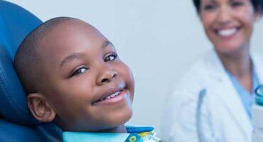 child in dentist chair getting sealants