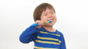 child brushing his teeth with a toothbrush